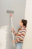 Teen girl paints the wall Royalty Free Stock Images