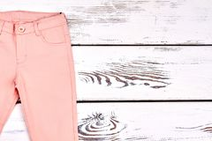 Teen girl peach color trousers. Girls colored summer skinny pants on wooden bacground, copy space. Light cotton pants on white wooden background royalty free stock image