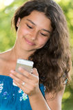 Teen girl with a phone in  park Royalty Free Stock Images