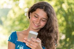 Teen girl with a phone in  park Stock Image