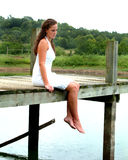 Teen Girl on Pier. Teenage girl sitting on pier looking into the water on a cloudy day Royalty Free Stock Image