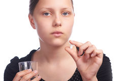 Teen girl with pill and water  in glass Stock Photo