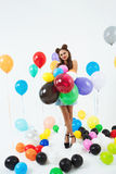 Teen girl in pin-up clothes holding bunch of balloons. Nice teen girl in pin-up clothes holding bunch of balloons looking srtraight at camera Stock Photos