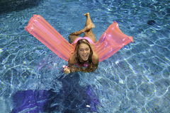 Teen girl in pink bikini on a float Stock Images
