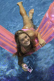 Teen girl in pink bikini on a float Stock Photography