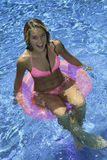 Teen girl in pink bikini on a float Royalty Free Stock Images