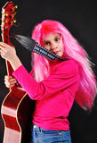 Teen girl with pink hair playing guitar Stock Images