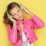 Teen girl in pink listening music. Teen girl in pink leather wear listening music on headphones.beautiful young girl.Green headphones Royalty Free Stock Photos
