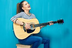 Teen girl play on guitar and emotional sings. Blue wall back Stock Photos