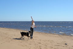 Teen girl playing with a dog in the sand. On the seashore Stock Photo