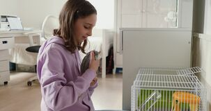 Teen girl playing with domesticated rat at home