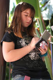 Teen girl playing electronic game. A 12 year old caucasian girl plays with her electronic hand-held game. She was also text messaging Stock Photography