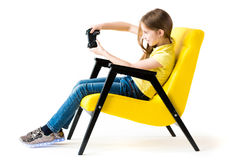 Teen girl playing with joystick in comfy chair Stock Image