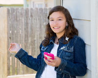 Teen girl playing music with smartphone earings Royalty Free Stock Images