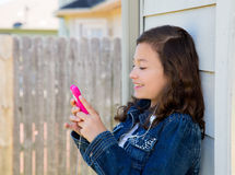 Teen girl playing music with smartphone earings Stock Images