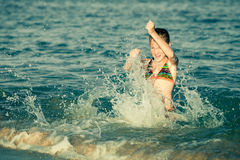 Teen girl playing at the sea Stock Images