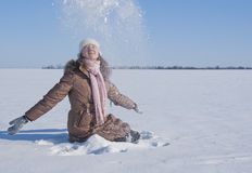 Teen girl playing with snow. Teen girl  sitting and playing with snow Stock Image