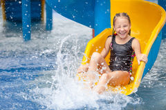 Teen girl playing in the swimming pool on slide Stock Photo