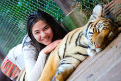 Teen girl playing with tiger cub inside cage Royalty Free Stock Image