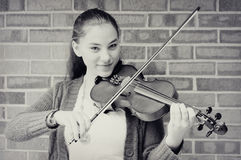 Teen Girl Playing Violin. A monochrome portrait of a teenaged girl playing violin by a brick wall.  She is smiling while she plays Stock Images