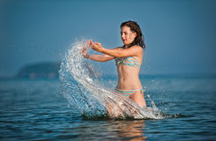 teen girl playing with waves at the beach. Royalty Free Stock Photo