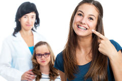 Teen girl pointing at dental barces with doctor in background. Royalty Free Stock Photos