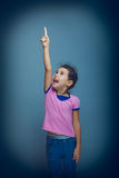 Teen girl pointing at the sky gray background Stock Photography