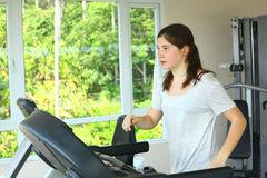 Teen girl with pony tail jogging on treadmill Royalty Free Stock Image