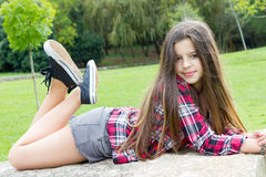 Teen girl portrait. Beautiful teen girl laying on a rock in the park Royalty Free Stock Image