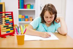 Teen girl practicing and doing homework Stock Photos