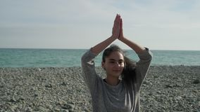 Teen girl is practicing yoga exercises in sea shore in daytime. Adolescent girl is training in morning time in beach of sea. She is folding hands near chest and stock footage