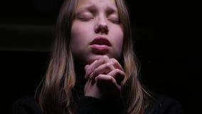 Teen girl praying. Beautiful sad teen girl praying stock video footage