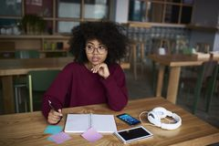 Teen girl preparing to exams in university concentrated on creating report for lesson Stock Photo