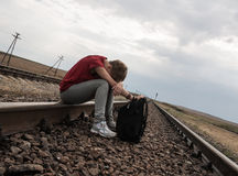 Teen girl with problems sitting on rail road royalty free stock image