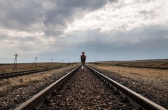 Teen girl with problems walking on rail road Stock Image