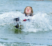 Teen Girl Pulling Up on  a Waterski. A young teen girl being pulled up behind a boat, she is on a trick ski and the determination on her face shows how hard she Royalty Free Stock Images
