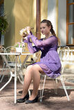 Teen girl in a purple dress holding a python Royalty Free Stock Photography