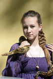 Teen girl in a purple dress holding a python Royalty Free Stock Images