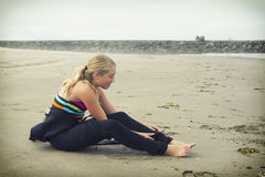 Teen girl putting on a wetsuit at Rockaway Oregon Royalty Free Stock Photography