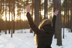 Teen girl raised hands from behind in winter pine forest in sunset Stock Photo