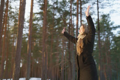 Teen girl raised hands in winter pine forest in sunset Stock Images