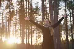 Teen girl raised hands in winter pine forest in sunset Stock Image