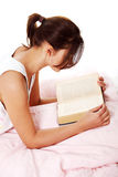 Teen girl reading in bed. Stock Images