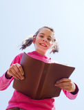 Teen girl reading the Bible. Against blue sky Stock Photo
