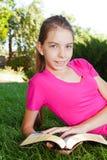 Teen girl reading the Bible outdoors Stock Photo