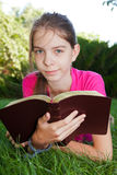 Teen girl reading the Bible outdoors Stock Photo