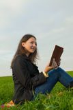 Teen girl reading the Bible outdoors Royalty Free Stock Image