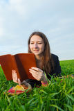 Teen girl reading the Bible outdoors Stock Photography