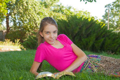 Teen girl reading the Bible outdoors Stock Photos