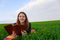Teen girl reading the Bible outdoors Royalty Free Stock Images